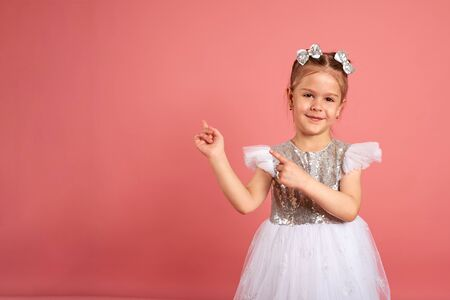 Portrait of a cute little girl in a beautiful dress that shows somewhere with her hands Imagens - 150114125