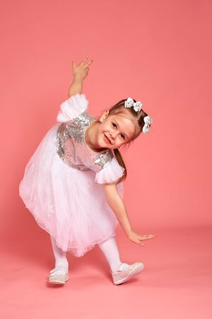 Little girl in a beautiful dress dancing over a pink background in the studio. Stok Fotoğraf