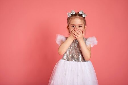 Little girl in a beautiful dress closes her mouth with her hands holding back a laugh Stok Fotoğraf