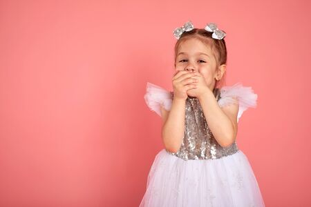 Little girl in a beautiful dress closes her mouth with her hands holding back a laugh Imagens - 150114129