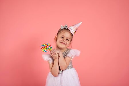 Happy smiling child with tasty lollipop having fun over pink background. Stok Fotoğraf
