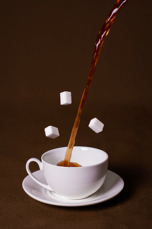 White cup on a brown background. Sugar levitation.