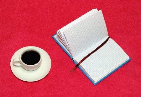 The cup of coffee and open notebook on a red blanket photo