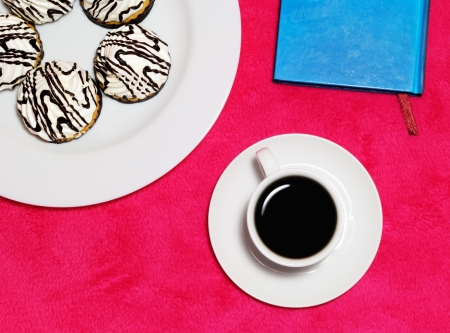 The composition of a cup of coffee, cakes and a notebook on a pink blanket Stock Photo - 20821894