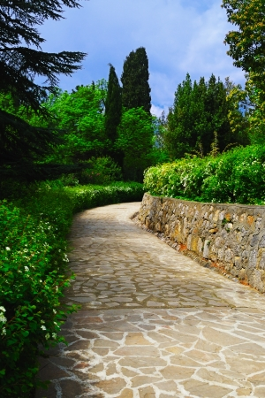 Stone walkway and a lush green vegetation in a Vorontsov park in the spring, Crimea