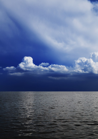A beautiful dark blue sky with fluffy clouds above the grey sea photo