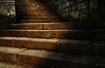 Stone dark stairs upwards with a streak of sunlight in Nikitsky Botanical garden in Crimea 版權商用圖片