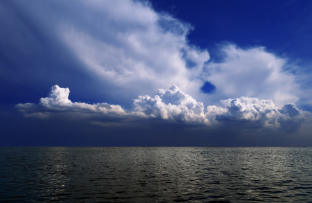 Dramatic dark blue sky with expressive clouds over the gray sea