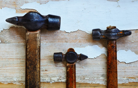 wizened: Three old hammer of different sizes lie on the board with traces of old paint