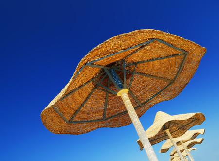 calor: Varios sombrillas de playa de mimbre, que se encuentra en la playa en Egipto en un d�a despejado caluroso y soleado