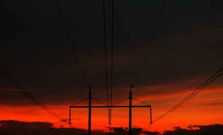 isolator insulator: Single-circuit high voltage power line at sunset on a background of beautiful orange sky