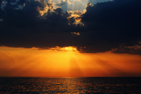 Beautiful spectacular sunset over the sea - the sun breaks through the clouds