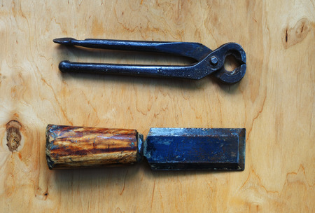 Old tool for carpentry - chisel and tongs lying on the plywood surface
