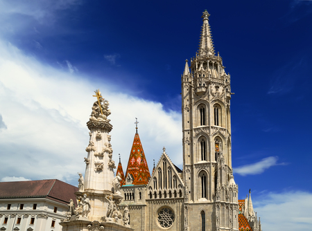 View on the main facade of the Matthias Church and Holy Trinity column located on the square in front of him, in the complex of the Buda castle, Budapest, Hungary