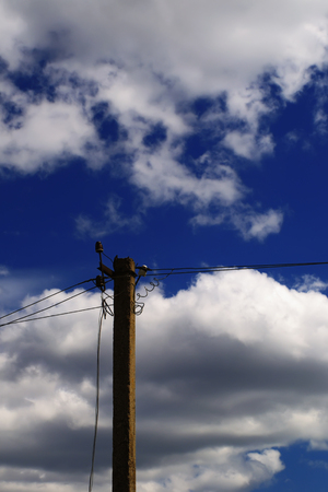 Concrete voltage electric pole with wires against the background of picturesque cloudy sky in the summer day