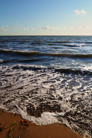 Picturesque sea landscape - waves lapping on a sandy beach on a warm summer evening