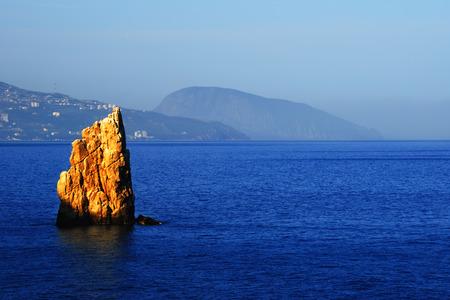 Scenic seascape - a lonely rock in the Black sea at sunset, illuminated by the sunlight, near the coast of Yalta, Crimea Фото со стока