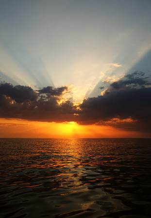 Beautiful seascape, the sun sets behind the clouds and forms rays in the sky, Black sea