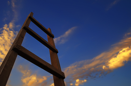 Wooden ladder, directed to the blue sky with clouds at sunset Фото со стока