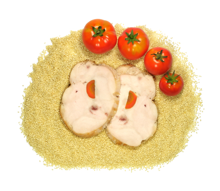 Two pieces of chicken with tomatoes, lying on a heap of sesame seeds, isolated on white background