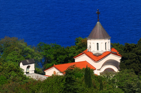 Beautiful summer landscape - the church Covers of the Blessed Virgin surrounded by lush green vegetation, Oreanda, Crimea