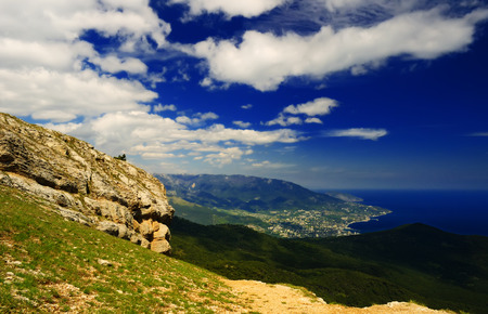 Picturesque Crimean landscape - view on Yalta and the surrounding mountains and cloudy sky from the top of Ai-Petri mountain on a sunny day in early spring, Crimea Фото со стока