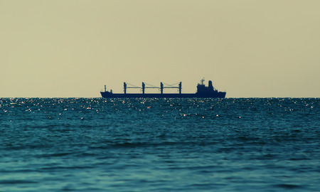 Silhouette of a cargo bulk-carrier on the horizon, on a sunny day, the Black sea Фото со стока