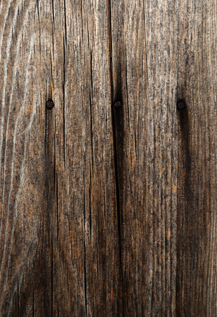Old cracked board with three rusty nails closeup Фото со стока