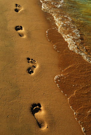Far-reaching row of footprints in the sand from the feet of the man on the beach on a summer evening