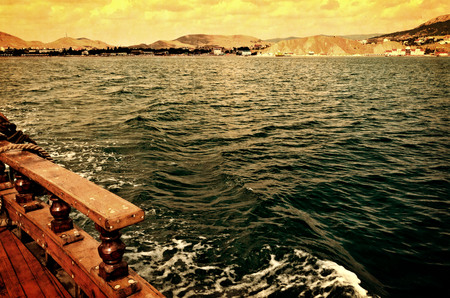 View of the coast of the Black sea from the deck of a wooden pleasure craft-photography with aging effect Фото со стока