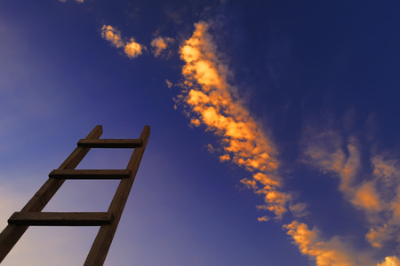 Concept - wooden ladder directed to the blue sky with clouds at sunset
