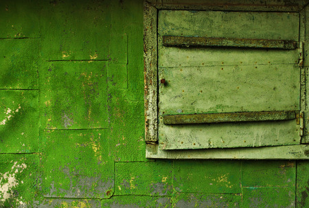 Old building - closed window and part of the wall, covered with a green cracked paint