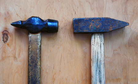 Two old hammer of different shape lie on the plywood