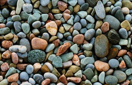 Natural background - multicolored sea pebbles on the beach closeup