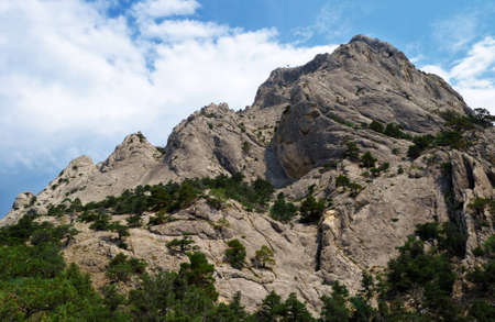 Beautiful mountain landscape - bottom view on the mountain spurs of the Kush-Kaya and cloudy sky, Crimea, Ukraine