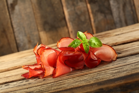 slices of prosciutto ham on wooden background