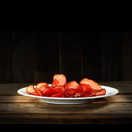 white plate with parma ham on dark wooden background