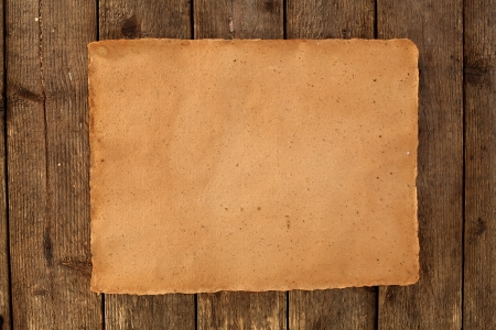 parchment on wooden wall background photo