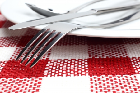 cutlery on white plate on red table cloth photo