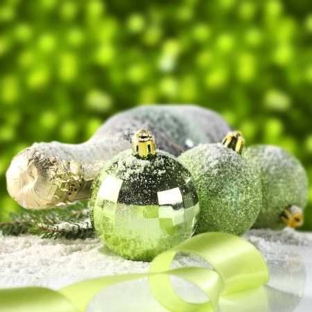 bottle of champagne and baubles with green background photo