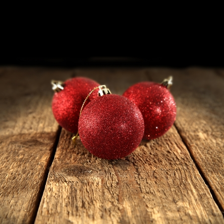 three red baubles on black background photo