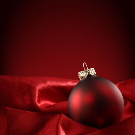 red bauble on deep red background photo