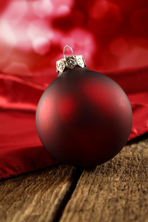 red bauble on velvet and wood photo