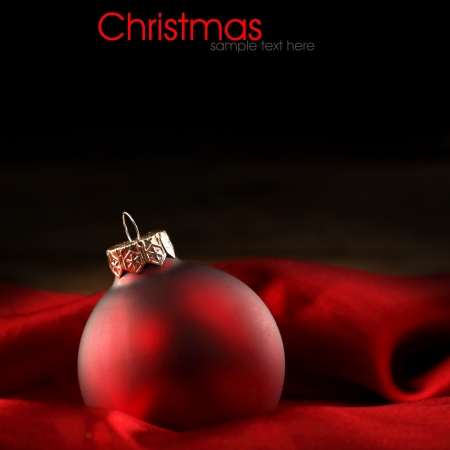 single red christmas decoration on velvet fabric photo