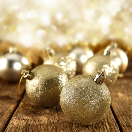 glitter gold baubles on sparkly background photo