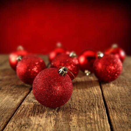 red glitter baubles spread on rustic table photo