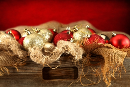 wooden drawer with baubles on red background photo