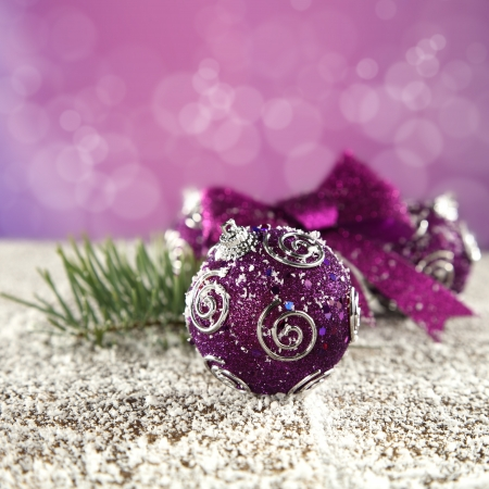 purple baubles on snow and purple background photo
