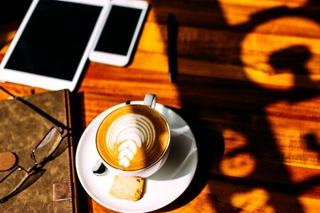 A cup of fragrant cappuccino, before a business meeting. Notebook. tablet and phone for communication Stok Fotoğraf