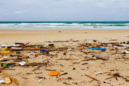 Garbage on the shore of a beautiful sea beach, environmental pollution, lots of plastic bottles, polystyrene foam, environmental problem. Waves moving ashore Stock Photo